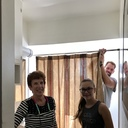 Tim hangs the shower curtain while Denise and Rachel supervise.